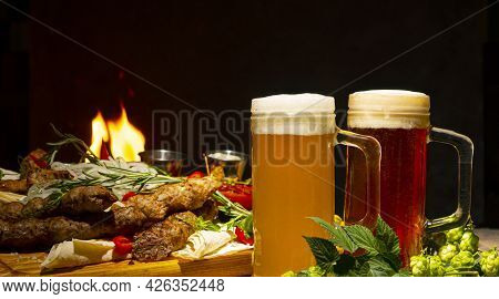 Glass Of Foamy Dark Beer And Light Beer On A Background Of Grilled Meat And Vegetables
