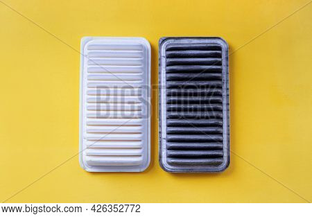 Car Air Filter Change Concept. Clean New And Old Dirty Automobile Air Filters On A Yellow Background