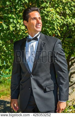 A Professional Executive Is Dressing In A Black Tuxedo, Confidently Looking Forward.