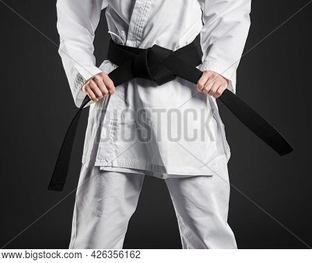 Karate Fighter Proudly Holding Black Belt. High Quality Beautiful Photo Concept