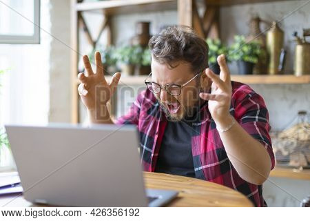Young Man Yells At The Laptop Monitor. Hes Got A Big Problem.