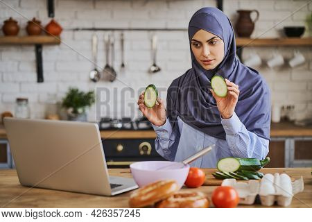 Young Arabian Woman Having A Video Call And Showing Slices Of Zucchini