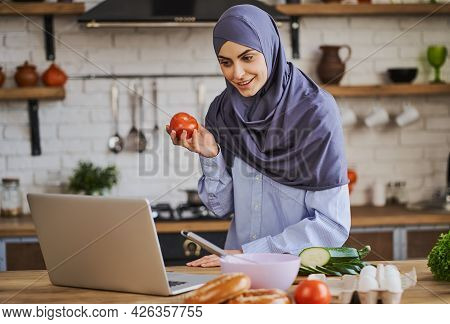 Young Muslim Woman Showing A Ripe Tomato To Her Friend During A Video Call