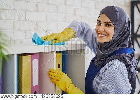 Pretty Muslim Woman Cleaning Bookshelves With A Rug In The Office