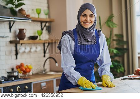 Portrait Of An Arabian Housewife Cleaning A Table In The Kitchen