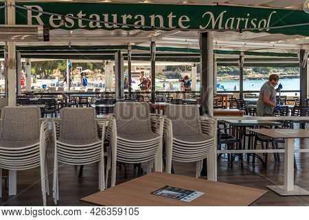 Colonia De Sant Jordi, Spain; July 02 2021: Restaurant Terrace On The Island Of Mallorca With A Woma