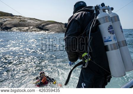April 17, 2021 - Hamburgsund, Sweden: A Scuba Diver Enters The Water. Ocean And Blue Sky In The Back