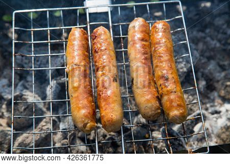 German Sausages Fried On A Metal Grill Against The Background Of Smoldering Coals Of The Grill. Cook