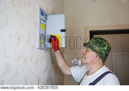 A Master Electrician In Overalls Checking The Switches In The Electrical Panel With A Screwdriver-in