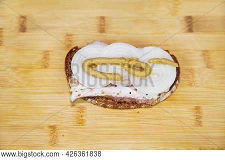A Sandwich Of Black Bread With Bacon, Onion And Mustard On The Background Of A Yellow Cutting Board.