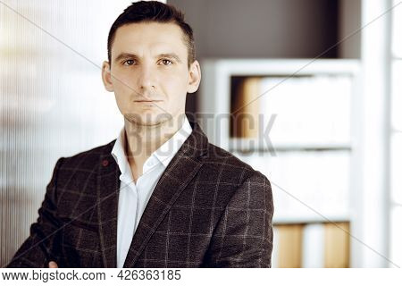 Friendly Adult Businessman In Grey Jacket. Business Headshot Or Portrait In Sunny Office