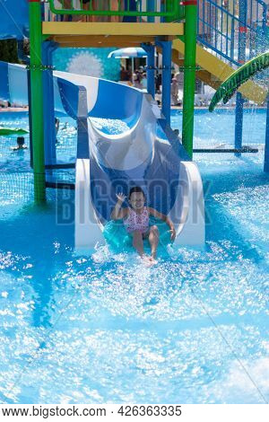 A Girl With Her Eyes Squeezed Shut Riding On An Inflatable Circle From A Water Slide In A Water Park