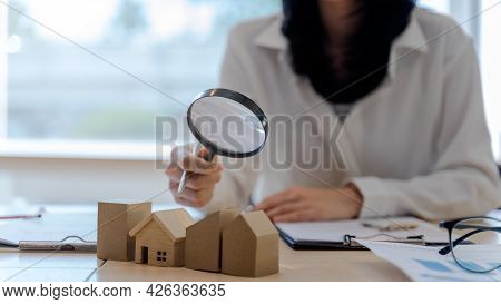 Assessor Woman Or Realtor Agents Use A Magnifying Glass To Checking House Model. Concept Of Real Est