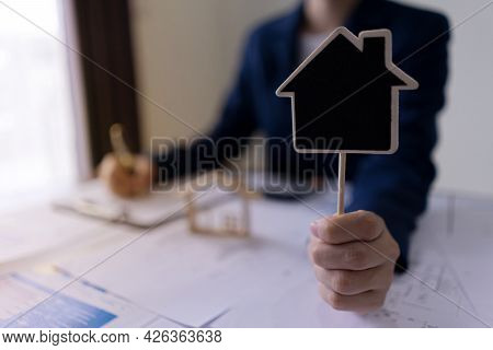 Real Estate Agents Showing House Labels With Copy Space For Sale Or Buy House. House Seller And Real