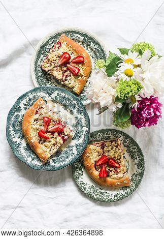 Pieces Of Yeast Dough Strawberry Rhubarb Sweet Pie With Crumbs On A Light Background, Top View
