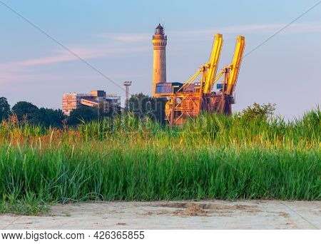 Swinoujscie. Old Lighthouse And Large Cranes In The Port.
