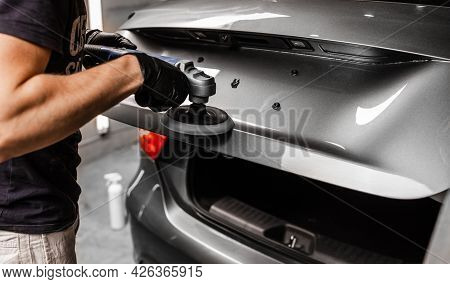 Car Detailing And Polishing Concept With Male Worker. Polishing Gray Luxury Car In Auto Service.