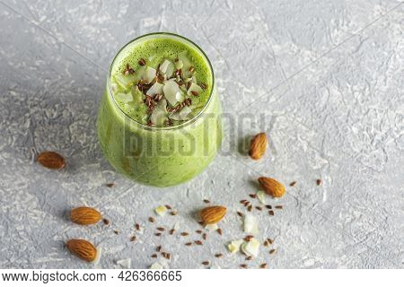 Glass With Green Smoothie From Spinach, Avocado, Celery, Kiwi And Coconut Milk, Served With Coconut
