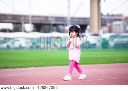 Cute Asian Girl Showing Insecure Or Embarrassed Expression. Children Walking On The Playground. Kid