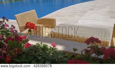 Selective Focus Summer Terrace With Wicker Rattan Chairs And Table Near Pool Resort. Red Geranium Fl