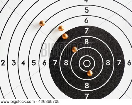 Balls Or Bullets For Pneumatic Shooting Lie On A Paper Target. An Illustration About Shooting From A