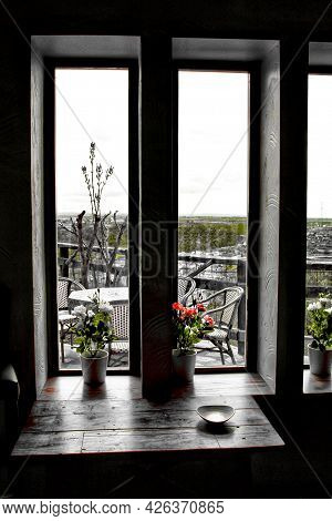 Mountains View Under Gray Sky Through The Window In Spring. Wooden Table And Pots In The Foreground