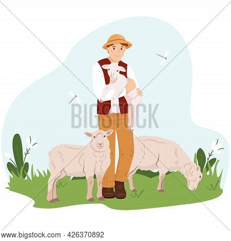 A Young Man Or Boy Farmer Holds A Young Lamb In His Arms. The Guy Takes Care Of The Sheeps. A Farmer