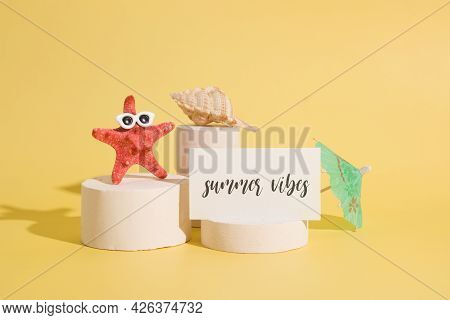 Starfish In Sun Glasses And A Card With The Text Summer Vibes On Pedestals On A Yellow Background. C