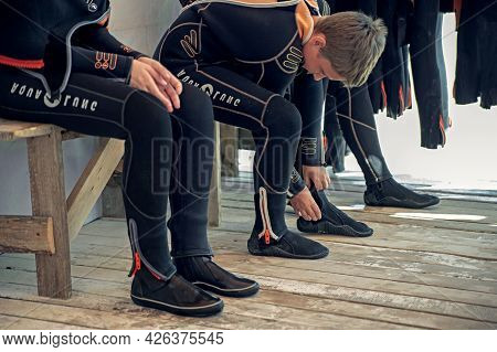 Anapa, Russia - June 20, 2019: Child Girl Puts On A Wetsuit And Prepares To Dive. Girl Scuba Diver.