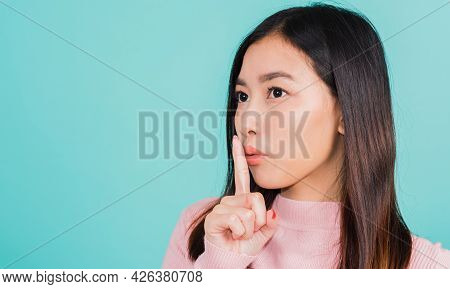 Young Asian Beautiful Woman With Finger In Front Of Mouth On Lips, Sign Of Silence Gesture Saying Sh
