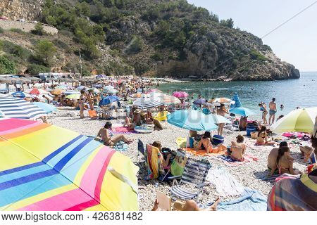 La Granadella  Spain - August 20 2016; Busy And Over-crowded Beach With Brightly Colored Sun Umbrell