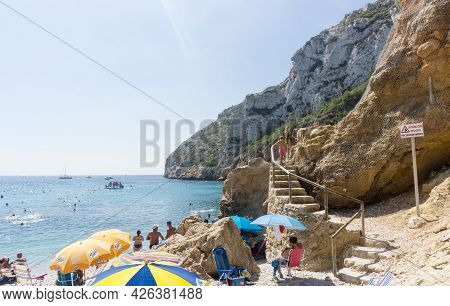 La Granadella  Spain - August 20 2016; Busy And Over-crowded Beach In Summer With Steps Cut Into Roc