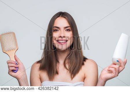 Young Beautiful Woman Combing Hair, Hold Shampoo Bottle And Comb. Hair Care. Beautiful Brunette Woma