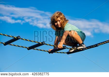 Cute Boy Climbs Up The Ladder On The Playground. Child Climbs Up The Ladder Against The Blue Sky. Be
