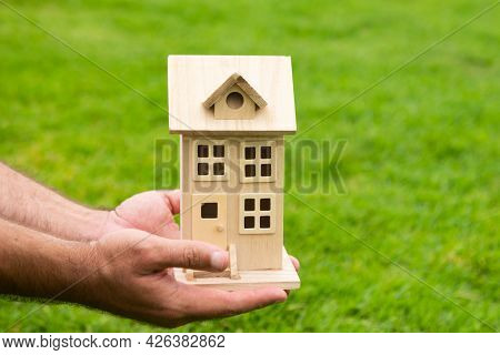 Hand Holding Model Of House Close Up. Small Miniature Toy House. Mortgage Property Insurance Dream M