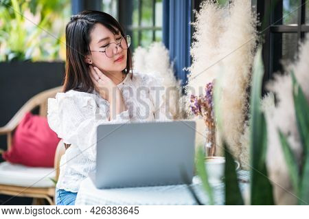 Asian Freelance People Business Female Touching Massaging Stiff Neck After Working With Laptop Compu