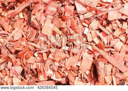 Red Decorative Chips, Wood Textured Background Top View. Shredded Tree Bark For Decorating A Garden