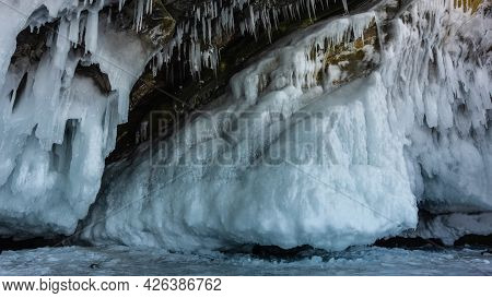 The Base Of The Granite Rock Is Covered With A Thick Layer Of Ice, Bizarre Icicles. Close-up. Detail