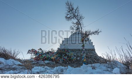 Ritual White Stupa On A Hill, Against The Blue Sky. Nearby Are Bare Trees And Bushes, Tied With Mult