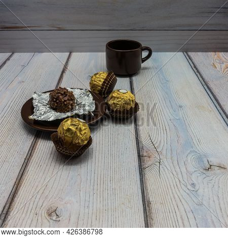 On A Wooden Table Is A Brown Porcelain Saucer With Unrolled Chocolate. Nearby A Cup And Three Candie