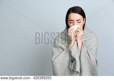 Young Woman With Blanket Suffering From Runny Nose On Light Grey Background. Space For Text
