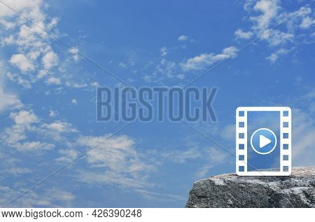 Play Button With Movie Flat Icon On Rock Mountain Over Blue Sky With White Clouds, Business Cinema O