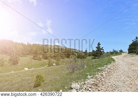 Dirt Rocky Road Through The Yalta Mountain Reserve. Ay-petri Yayla And A Mountain With White Domes O