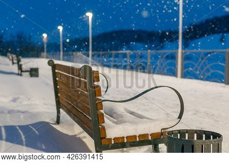 Snowfall In The Park In Winter, Benches Covered With Snow Standing In A Row. Selective Focus On The
