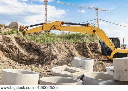 An Excavator Digs A Foundation Pit For The Construction Of A Residential Building. New Residential B