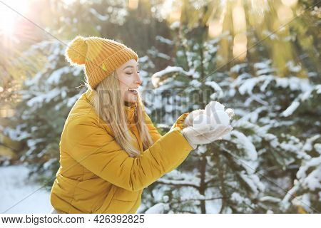 Woman Holding Snowballs Outdoors On Winter Day