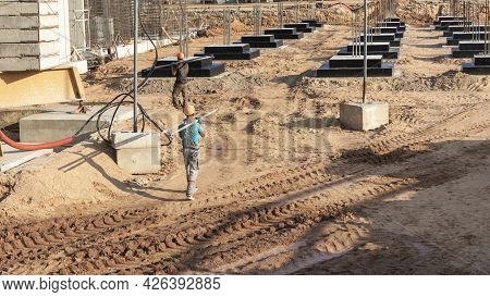 A Worker Transfers Elements For The Installation Of The Formwork At The Construction Site. Monolithi