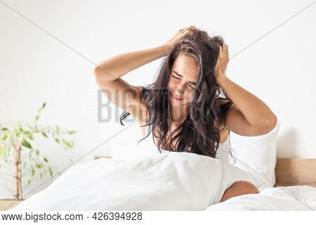 Unhappy Woman Holds Her Head As She Wakes Up After Insufficient Sleep In The Bed.