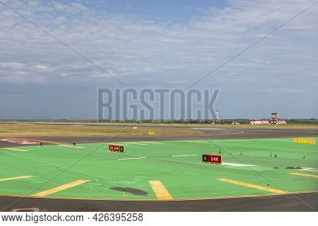 Runway Of Airport With Cloudy Sky And Print Of Wheels At The Surface