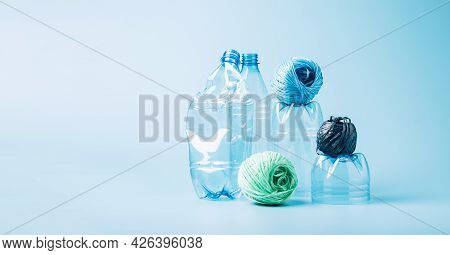Plastic Recycling And Reuse Concept. Empty Plastic Bottle And Polyester Fiber Synthetic Thread On A